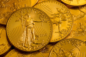 Pile of golden coins with Liberty on US Treasury issue Gold Eagle one ounce pure gold coin