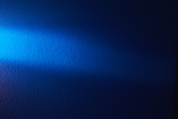 A beam of light blue light horizontally shines on a blurry textural blue background