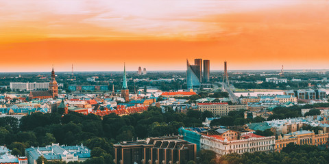 Riga, Latvia. Top View Panorama Skyline Cityscape At Sunset Light. Dome Cathedral, Basilica Of St. James, Vansu Bridge