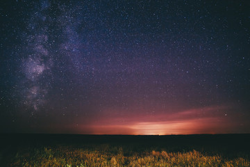 Night Starry Sky Above Field And Yellow City Lights On Background. Night View Of Natural Glowing Stars