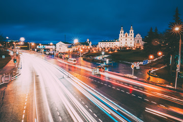 Minsk, Belarus. Night Traffic On Illuminated Street And  Cathedral Of Holy Spirit In Minsk. Famous And Main Orthodox Church Of Belarus At Evening. Famous Landmark.