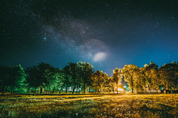 Green Trees Woods In Park Under Night Starry Sky. Night Landscape With Natural Real Glowing  Milky Way  Stars Over Meadow At Summer Season. View From Eastern Europe At Spring Season