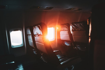 Sun Shining From Airplane Aircraft Plane Window In Cabin Cabin. Bright Sun Rays At Sunset Sunrise