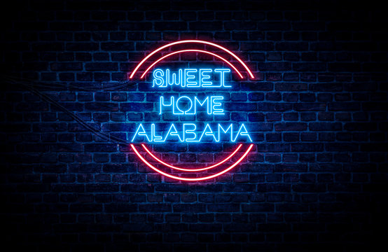 A sign showing Alabama state slogan, in blue and red neon light on a brick wall background and wires on the side.