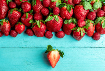 Strawberries on a blue table above view. Fruits flat lay image