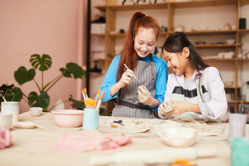 Portrait of two happy girls shaping clay while making handmade ceramics in pottery class, copy space