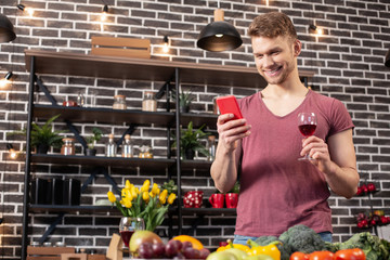Man holding smartphone and glass of wine waiting for girlfriend at home