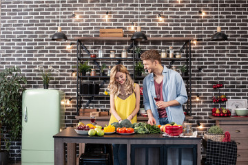 Blonde-haired woman with wavy hair enjoying cooking time with her man