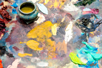 Paints of different colors on a multi-colored palette of mixed oil paints
