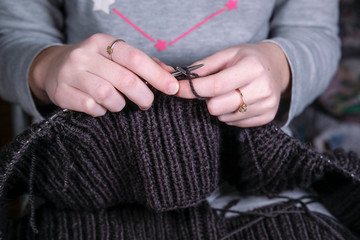 image of a girl knitting on metal knitting needles