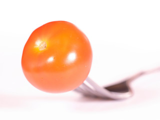 image of a tomato pinned on a fork