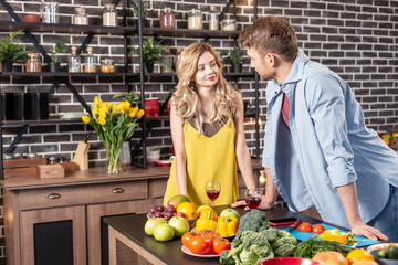 Good-looking young couple standing near the table in the kitchen