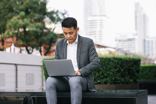 Serious Asian middle-aged businessman sitting outdoors and working on his laptop.