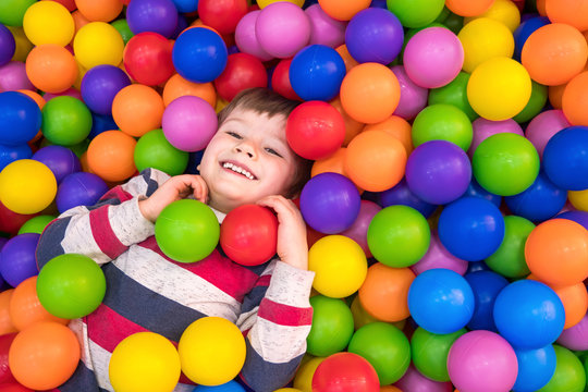 Little boy playing in dry pool with plastic balls in the nursery. Close-up leisure activities indoors. Positive emotions background. School holidays. Copy space