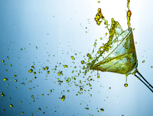 High Speed Liquids Photography. Colofur Drink Droplets Poured Out of The Clear Wine Glass.
