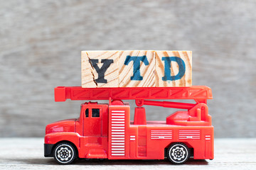 Red fire truck hold letter block in word YTD (abbreviation of year to date) on wood background