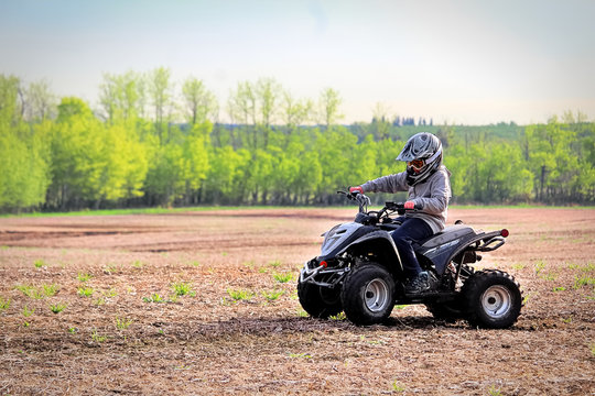 A young boy quading in a spring field
