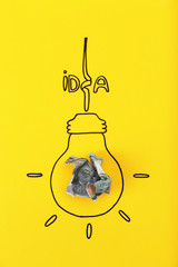 Composition with crumpled banknote, drawing of lamp bulb and word IDEA on color background. Creative concept