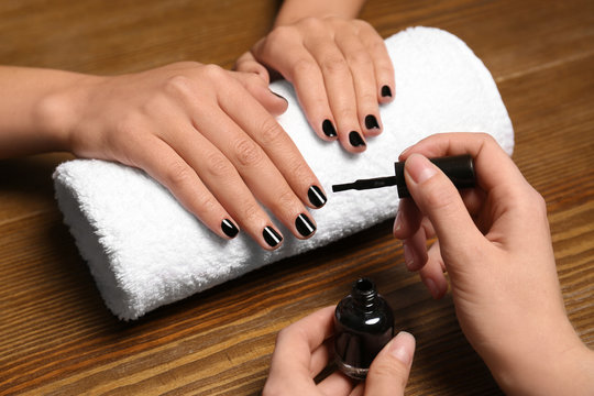 Manicurist painting client's nails with polish in salon, closeup