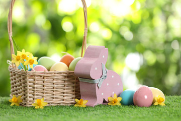 Cute wooden Easter bunny with wicker basket and dyed eggs on green grass against blurred background, space for text