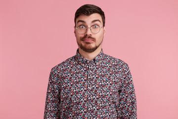 Surprised man stares through spectacles with misunderstanding, bewilderment, wearing colorful shirt shrug shoulders in uncertainty, over pink background Wall mural