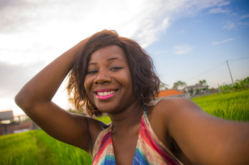 happy and attractive black afro American woman in beautiful dress taking selfie portrait with internet mobile phone enjoying holidays travel in Asia  smiling cheerful at rice field