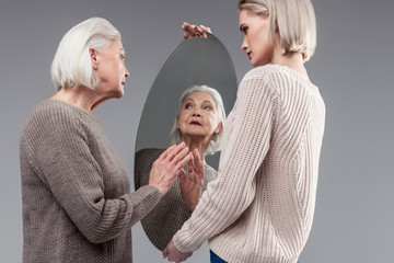 Beaming grey-haired woman touching clean surface of round mirror