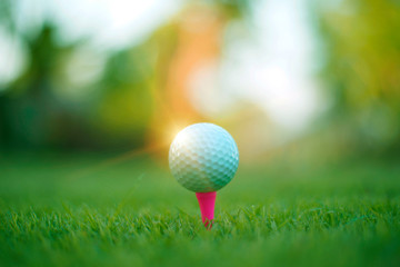 Golf ball on tee in beautiful golf course with sunset background.