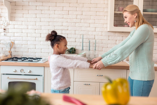 Mother and daughter feeling happy while dancing after breakfast