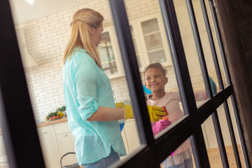 Mother wearing yellow gloves cleaning house with daughter