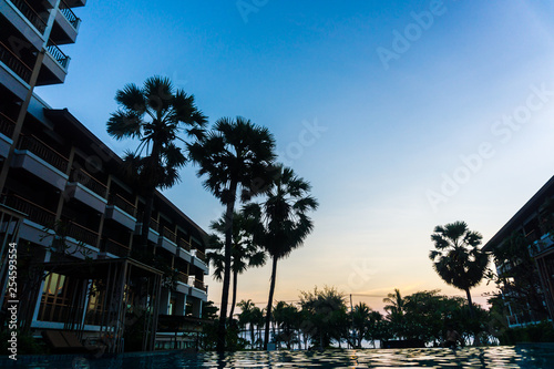 Silhouette Palm Tree Sunset In Modern Resort With Swimming