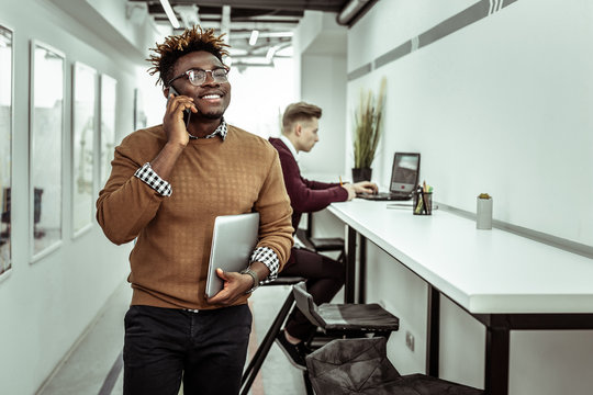 Self-conscious African American guy talking on mobile phone