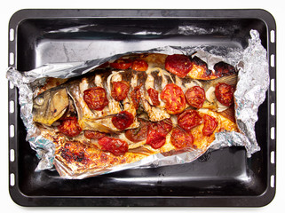 Baked fish in the oven with tomatoes