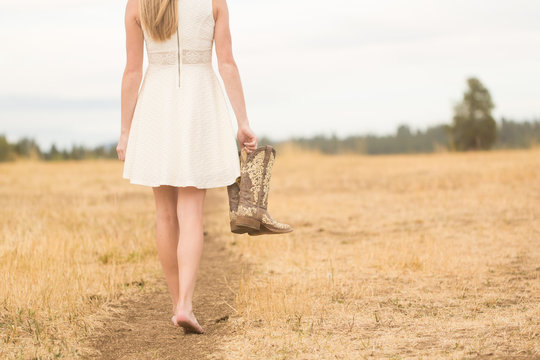 Young woman walking on path holding boots