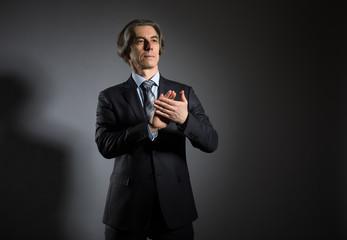 A grown man in an elegant suit claps his hands against a dark background. Businessman applauds.