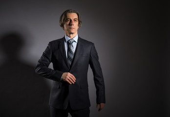 Man 50 years old in an elegant suit on a dark background. Men's fashion.
