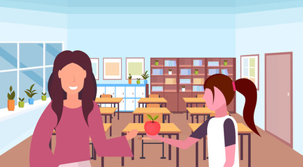 schoolgirl giving apple to woman teacher education concept modern school classroom interior female characters portrait horizontal flat