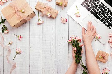 Workspace with a laptop keyboard, rose flowers, gift boxes wrapped in kraft paper on wooden background. Copy space for text,  Top view, flat lay. Woman's hands typing