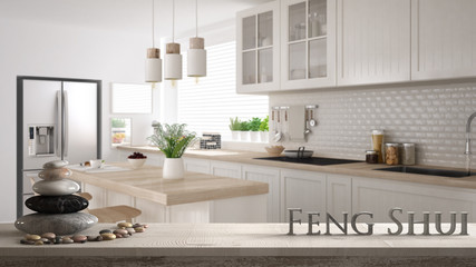 Wooden vintage table shelf with pebble balance and 3d letters making the word feng shui over blurred scandinavian white and wooden modern kitchen, zen concept interior design Wall mural