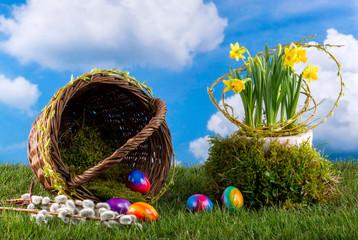 Symbolbild für Ostern, Weidenkorb mit bunten Eiern, Osterglocken auf grüner Wiese vor Wolkenhimmel