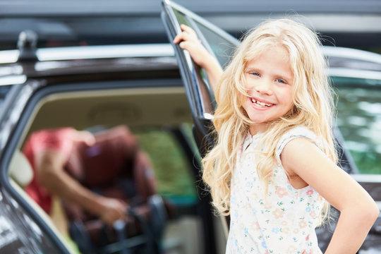 Mädchen am Auto freut sich auf die Reise