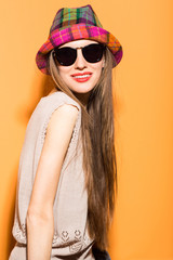 Happy young beautiful woman wearing sunglasses and hat over bright orange background