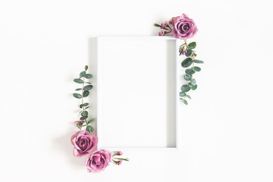 Flowers composition. Photo frame, eucalyptus branches and rose flowers on white background. Flat lay, top view, copy space