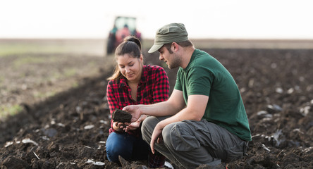 Young farmers exam dirt while tractor is plowing field