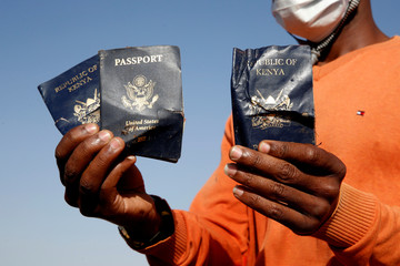 Man holds passengers' passports found at the scene of the Ethiopian Airlines Flight ET 302 plane crash, near the town of Bishoftu, near Addis Ababa