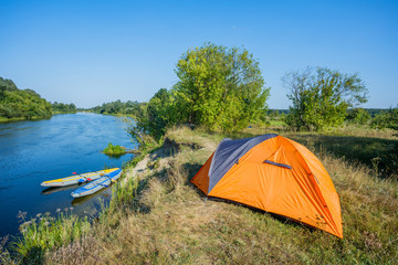 Kayaking. A tent camp stands on the river bank.