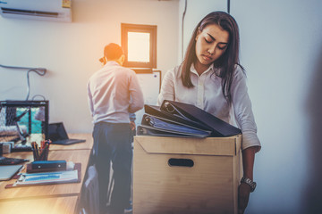 Sad fired businesswoman holding box with her stuff after being dismissed.