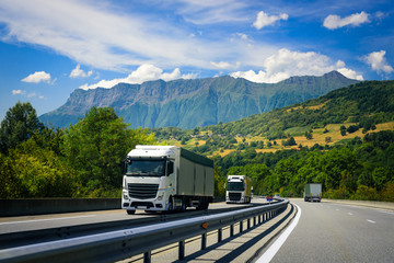 Trucks drive on the European highway on the Alpine mountains.