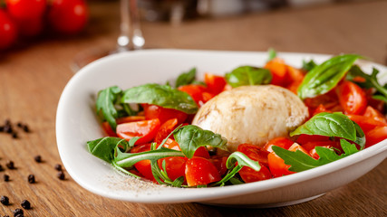Concept of Italian cuisine. Caprese salad with cherry tomatoes, arugula and basil salad mix, and mozzarella cheese. Serving dishes in white plate in a restaurant. background image.