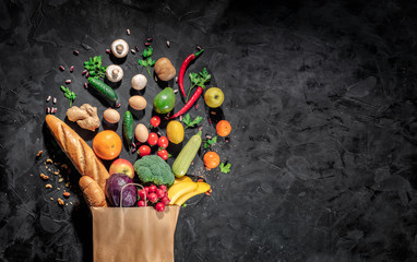 Healthy food in full paper bag of different products vegetables and fruits on dark background